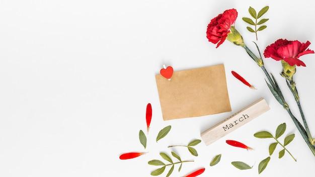 Inscription de mars avec des fleurs d'oeillets rouges et du papier Photo gratuit