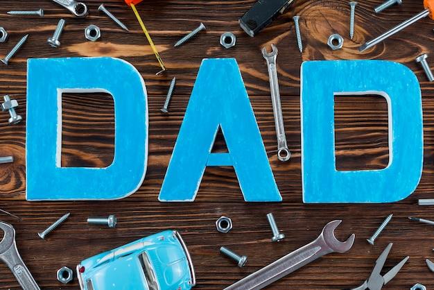 Inscription de papa avec différents outils et voiture de jouet Photo gratuit