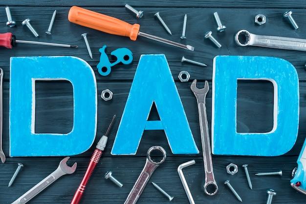 Inscription de papa avec des outils sur la table bleue Photo gratuit