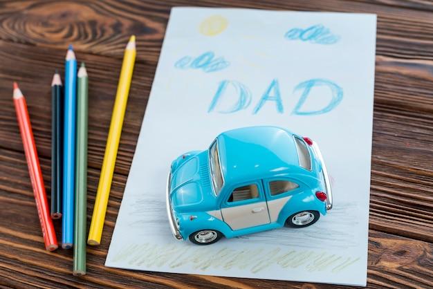 Inscription de papa avec voiture de jouet et crayons Photo gratuit