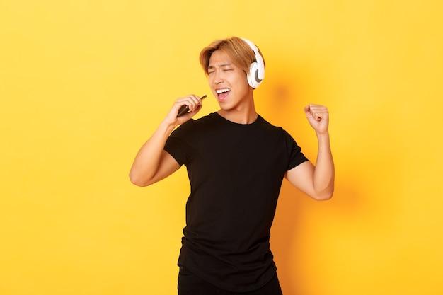 Insouciant Beau Mec Asiatique Dans Les écouteurs, Jouant à L'application De Karaoké, Chantant Dans Le Microphone Du Téléphone Mobile, Mur Jaune Debout Photo gratuit