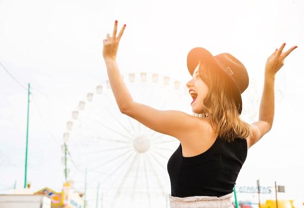 Insouciante jeune femme montrant le signe de la paix au parc d'attractions Photo gratuit