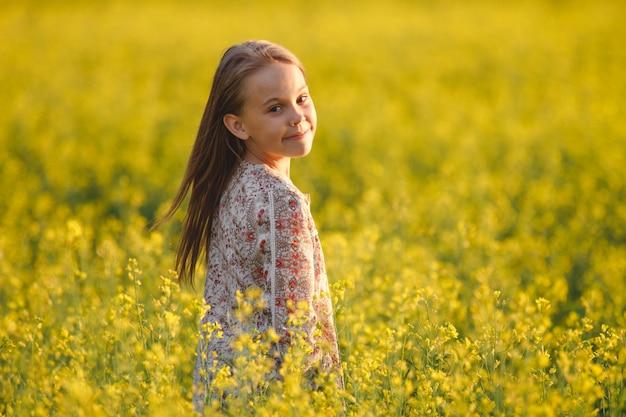 Insouciante jeune fille aime le coucher de soleil dans un champ Photo Premium