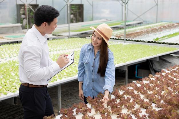 Les inspecteurs inspectent et enregistrent la qualité des légumes biologiques avec des agricultrices fournissant des conseils. Photo Premium