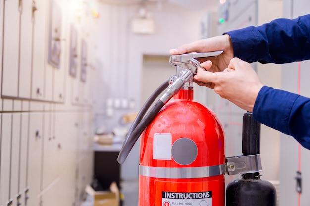 Inspection d'ingénieur extincteur dans la salle de contrôle. Photo Premium