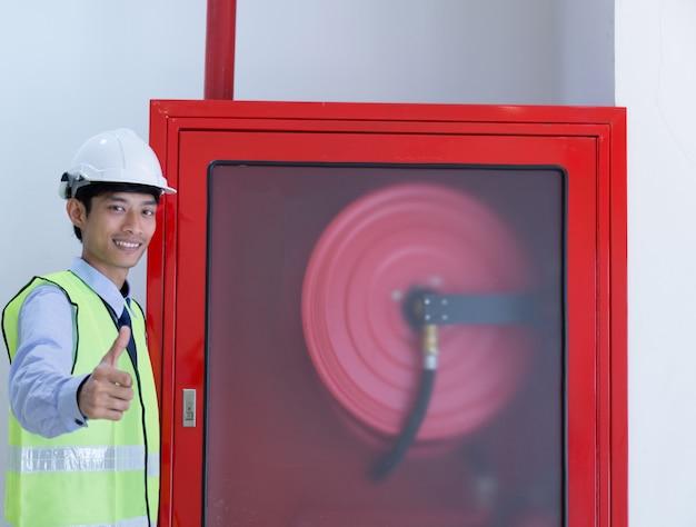 Inspection d'ingénieur extincteur et tuyau d'incendie. Photo Premium