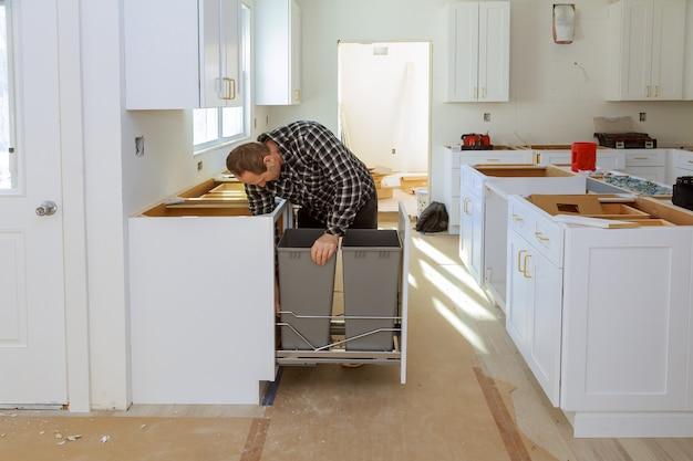 Installation d'une nouvelle table de cuisson à induction dans l'installation d'une cuisine dans une corbeille à papier moderne Photo Premium