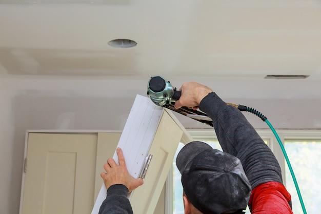 Installation des portes des pièces dans le travailleur du bois de la maison à l'aide d'un pistolet à clous Photo Premium