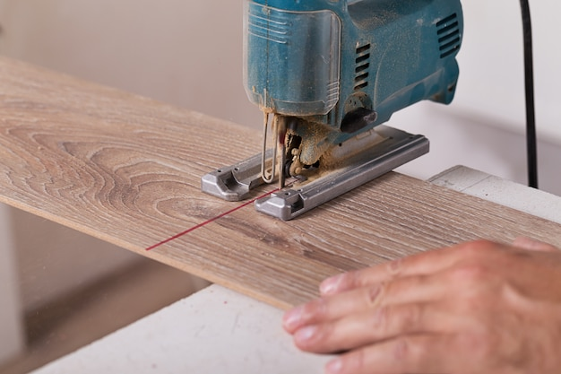 Installation de sols stratifiés. plancher de parquet coupé par charpentier Photo Premium