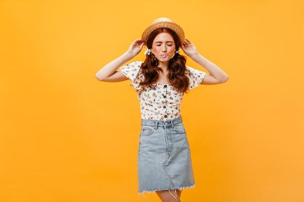 Instantané D'une Femme Vêtue D'une Jupe En Jean Et D'un Chemisier Blanc Sur Fond Orange. Femme En Plaisancier Gonfle La Bulle De Gomme. Photo gratuit