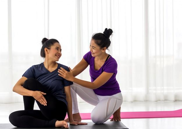 L'instructeur De Cours De Yoga Aide Le Débutant à Faire Des Exercices D'asana. Mode De Vie Sain Dans Un Club De Fitness. S'étirer Avec L'entraîneur Photo Premium
