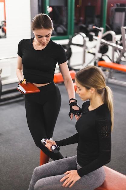Instructeur de gym guidant la femme pendant l'exercice avec haltère Photo gratuit