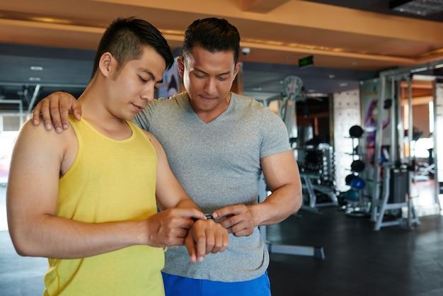 Instructeur de gymnastique masculin asiatique avec la main sur l'épaule du client en regardant son tracker de fitness Photo gratuit