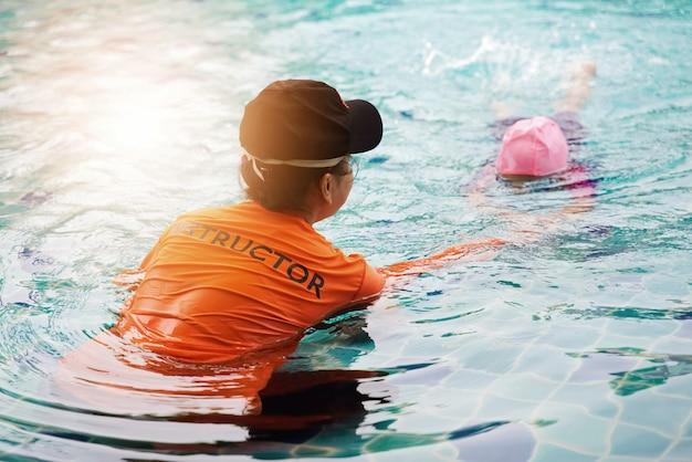 Une instructrice apprend à l'enfant à nager. Photo Premium