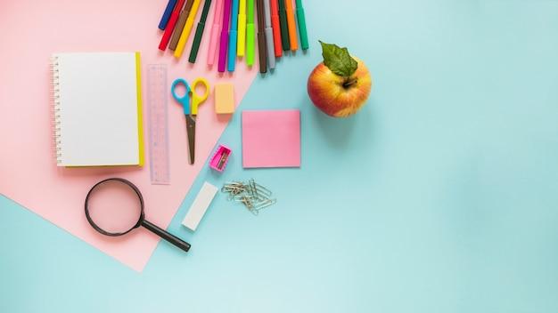 Instruments d'écriture et pomme posés Photo gratuit
