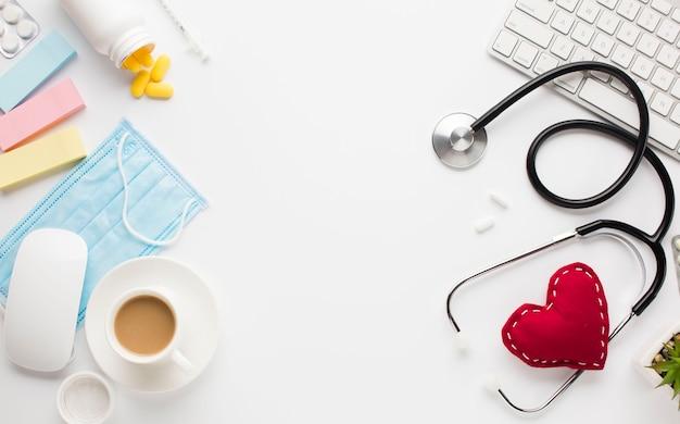 Instruments médicaux avec pilules près du cœur en tissu et équipement sans fil sur une surface blanche Photo gratuit