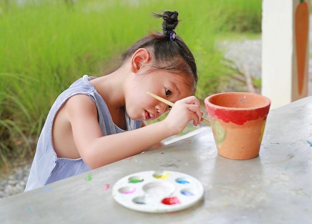 Intend enfant asiatique fille peinture sur plat en terre cuite. Photo Premium