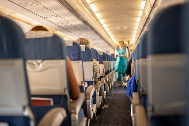 Intérieur de l'avion commercial avec des passagers sur leurs sièges pendant le vol. Photo Premium