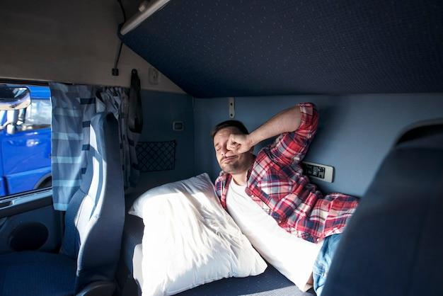 Intérieur De La Cabine Du Camion Avec Chauffeur Dormant Dans Son Lit Photo gratuit