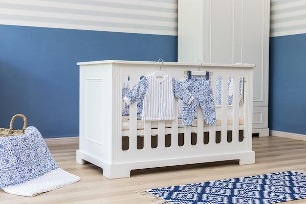 Intérieur de la chambre de bébé minimaliste avec une élégante, petite, chic, chaise, une échelle décorée Photo Premium