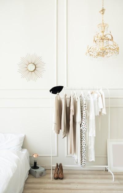 Intérieur De La Chambre Lumineuse à La Mode. Cintre Avec Des Vêtements Pour Femmes. Photo Premium