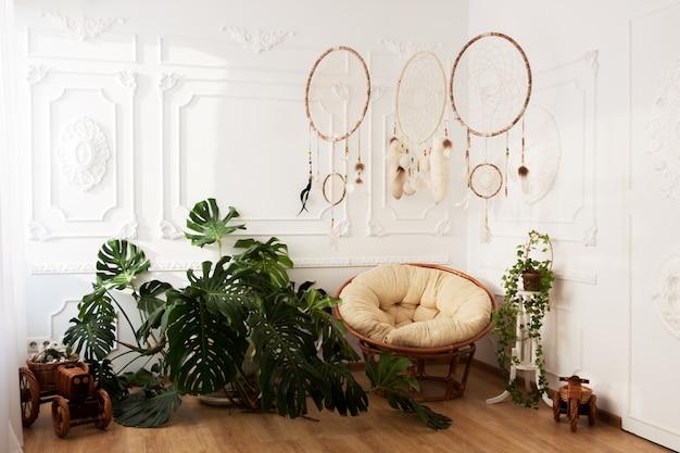 Intérieur de la chambre avec plantes tropicales monstera, dreamcatchers et chaise papasan Photo Premium