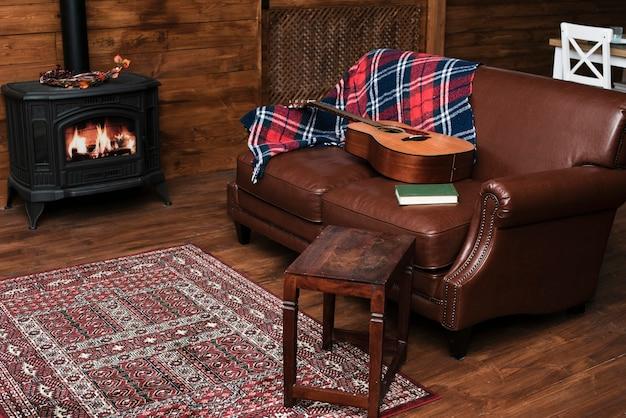Intérieur confortable avec guitare sur le canapé Photo gratuit