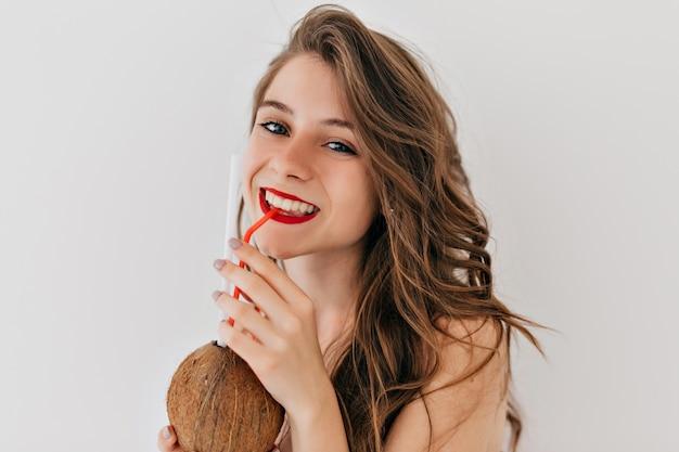 À L'intérieur D'une Femme élégante Et Heureuse Avec Des Lèvres Rouges Et Des Dents Blanches Et Une Peau Saine Avec Des Cheveux Bouclés Boit De La Noix De Coco Et Pose Photo gratuit