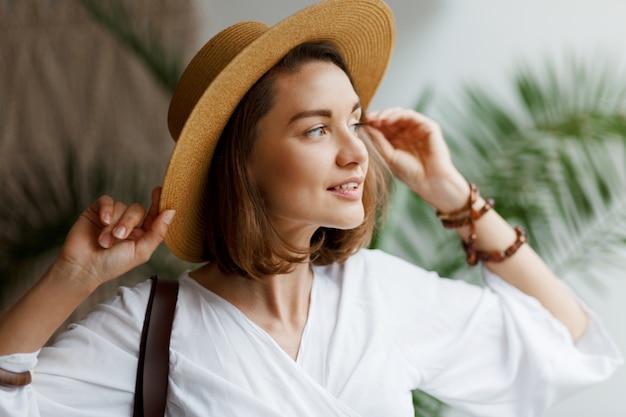 Intérieur Gros Plan Portrait D'élégante Jolie Femme En Chapeau De Paille Et Chemisier Blanc Posant à La Maison Photo gratuit
