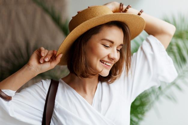 Intérieur Gros Plan Portrait D'élégante Jolie Femme En Chapeau De Paille Et Robe Blanche Posant à La Maison Photo gratuit