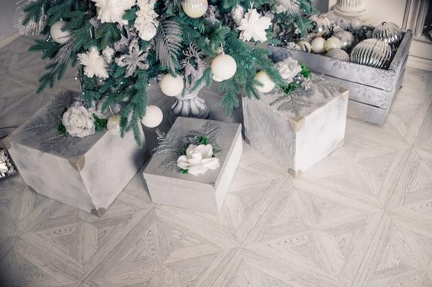 Intérieur de noël élégant avec un canapé élégant. maison de confort. présente des cadeaux sous l'arbre dans le salon Photo Premium
