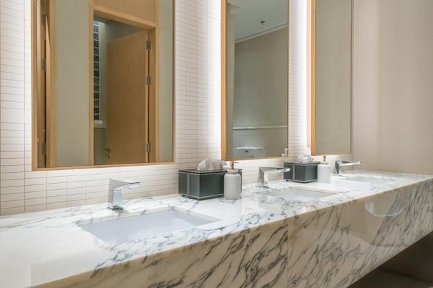 Intérieur de la salle de bain avec robinet de lavabo et serviette noire à l'hôtel. Photo Premium