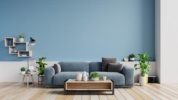 Intérieur d'un salon lumineux avec des oreillers sur un canapé, des plantes et une lampe sur un mur bleu vide. Photo Premium