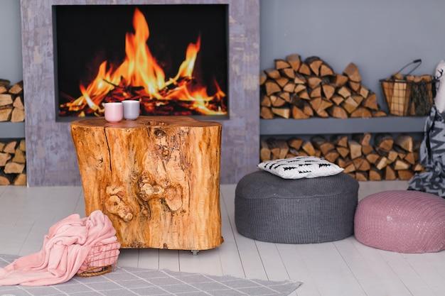 Intérieur scandinave avec une cheminée, une table en moignon, une pile de bûches pour le feu Photo gratuit