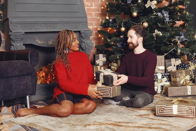 Les Internautes à La Maison. Couple Dans Une Décoration De Noël. Femme Africaine Et Homme Caucasien. Photo gratuit