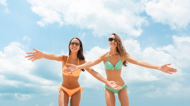 Interracial femme amis en bikinis coloré à la plage d'été Photo Premium