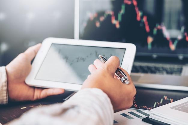 Investissement boursier entrepreneur homme d'affaires à l'aide d'une tablette pour discuter et analyser Photo Premium