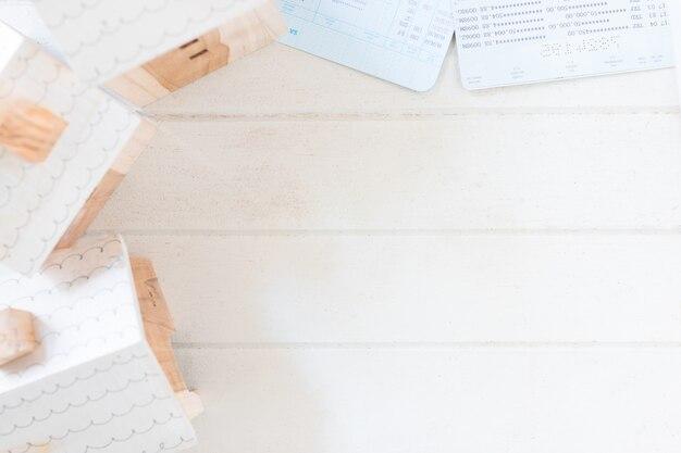 Investissement immobilier, modèle de maison miniature avec livre de comptes sur une planche en bois blanche Photo Premium