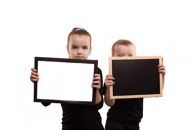 Isolé sur fond blanc garçon et fille en t-shirts noirs montrent des formulaires vierges Photo Premium