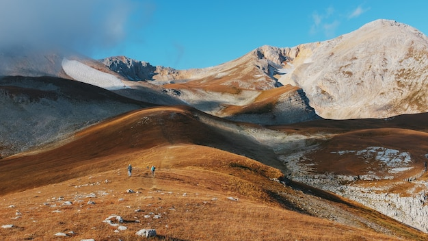 Un itinéraire à travers les sommets et les collines à travers des paysages majestueux avec des touristes et des voyageurs au loin. Photo Premium