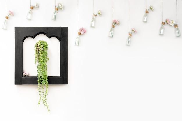 Ivy dans un cadre en bois noir sur un mur blanc avec des fleurs dans des bouteilles suspendues. Photo Premium