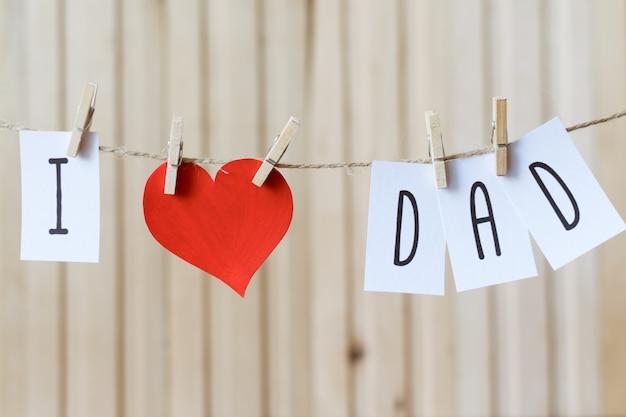 J'aime papa. message de la fête des pères avec coeur de papier suspendu avec des épingles sur une planche de bois clair Photo Premium