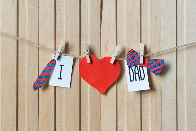 J'aime papa. notion de fête des pères. message avec coeurs de papier, cravate et noeud papillon suspendus avec des épingles sur une planche de bois clair. Photo Premium