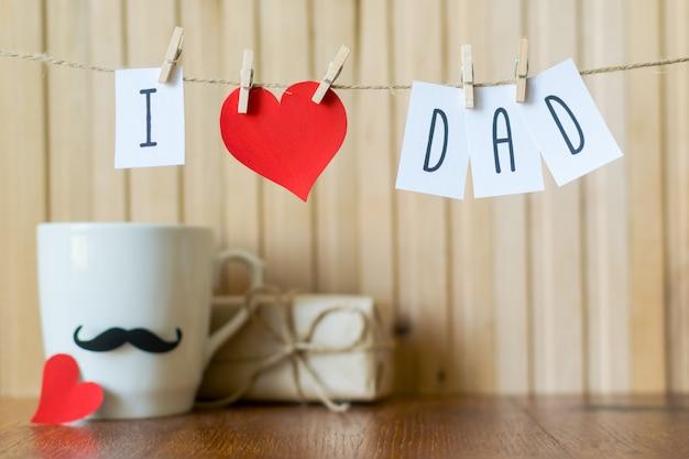 J'aime papa. voeux fête des pères. message avec coeur de papier suspendu avec des pinces à linge sur une planche de bois. Photo Premium