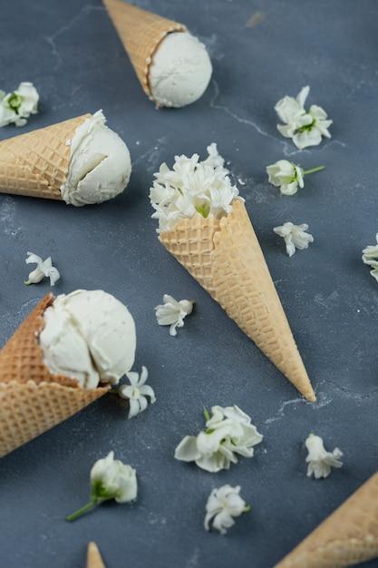 Jacinthe blanche et glace à la vanille dans les cônes de gaufres sur fond bleu. concept de motif Photo Premium