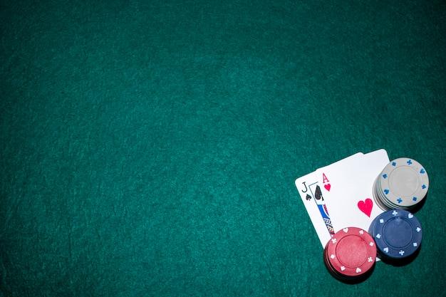 Jack de pelle et carte de coeur ace avec pile de jetons de casino sur table de poker vert Photo gratuit