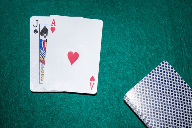 Jack de pique et de coeur ace carte à jouer sur la table de poker verte Photo gratuit