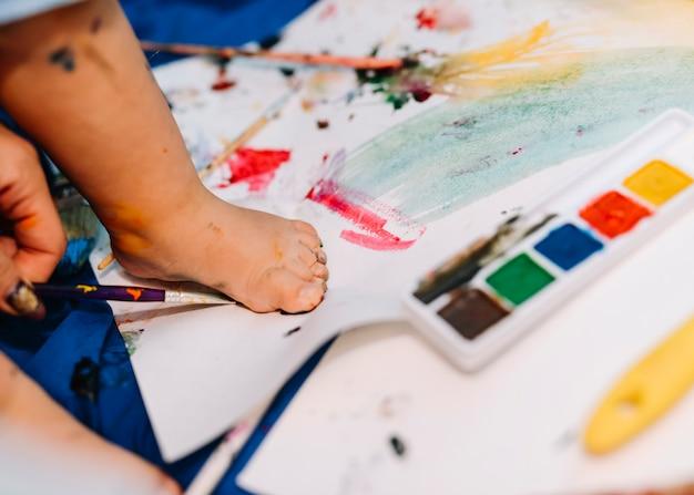 Jambe d'enfant sur du papier près de l'aquarelle Photo gratuit