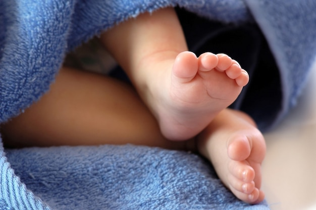 Jambes De Bébé De Quatre Mois Dans Une Serviette Bleue Photo Premium