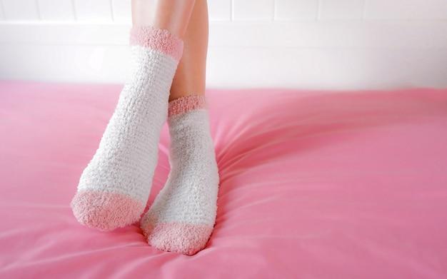 Les jambes d'une belle femme portent des chaussettes chaudes dans la chambre à coucher. chaussettes fashion roses. Photo Premium